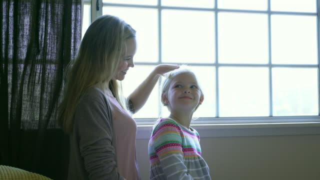 MS Mother brushing daughter's hair.