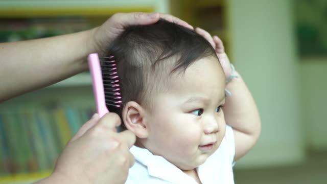 vidéos et rushes de mère brossant les cheveux sains pour bébé - coiffeur