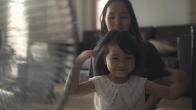 stockvideo's en b-roll-footage met moeder haar kleine dochter haar borstelen - kammen