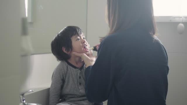 mother brushing her son's teeth in bathroom - nightwear stock videos & royalty-free footage