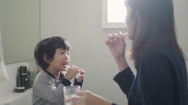 mother brushing her son's teeth in bathroom - brushing teeth stock videos & royalty-free footage