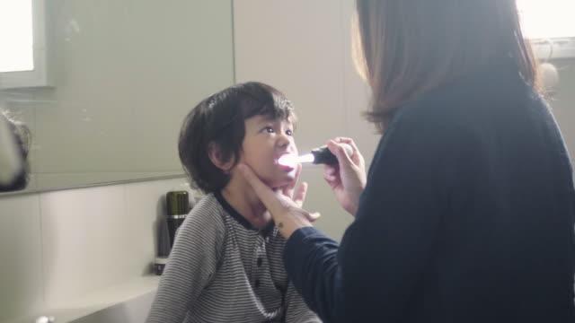 vídeos y material grabado en eventos de stock de madre cepillando los dientes de su hijo en el baño - cepillar los dientes