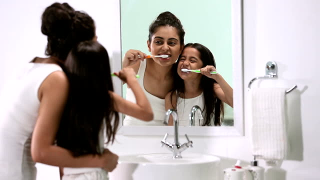 Mother brushing teeth with her daughter, Delhi, India