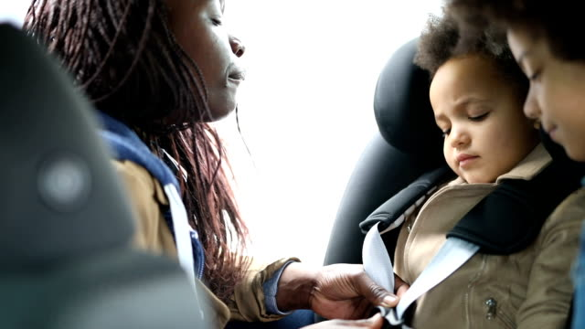 mother buckling her daughter into her car seat - preparation stock videos & royalty-free footage