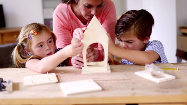 Mutter ein Vogelhaus mit ihren Kindern bauen