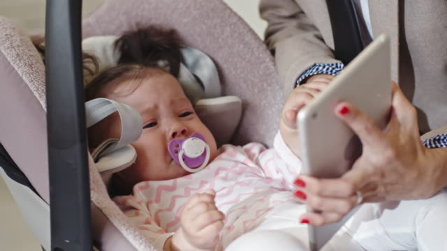 mother calming baby daughter with digital tablet - haarzopf stock-videos und b-roll-filmmaterial