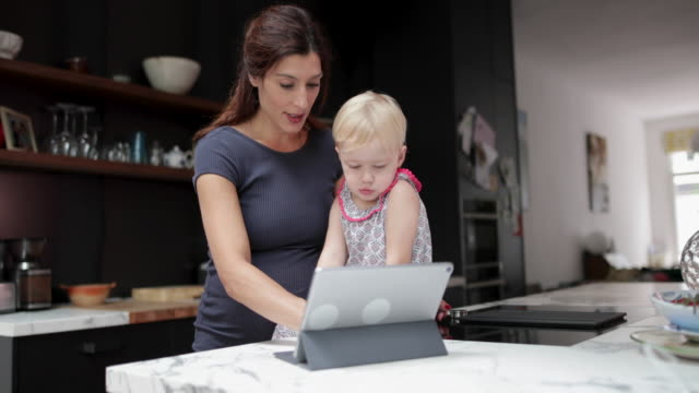 mother calming daughter with digital tablet - using digital tablet stock videos & royalty-free footage