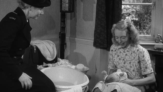 1952 montage mother caring for baby while nurse sits down and observes, child removing blanket and powder from a baby carriage, nurse and mother discussing her baby / wadhurst, england, united kingdom - wadhurst video stock e b–roll