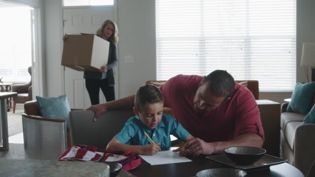 vidéos et rushes de une mère porte une boîte tandis que père aide fils à faire leurs devoirs - soulever