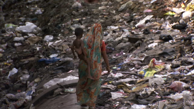 a mother carries an infant over a pipeline through a garbage heap. available in hd - india video stock e b–roll