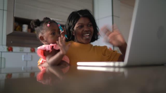 vídeos de stock, filmes e b-roll de mãe carregando filha bebê fazendo uma chamada de vídeo em casa usando tablet digital - sentir a falta emoção