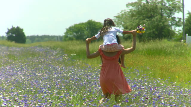 MS CU Mother carrying daughter on shoulders walking through meadow, Eastville, Virginia, USA