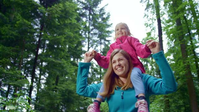 slo mo ts 母は娘を肩に乗せて、自然の中を歩きながら笑う - 肩に乗せる点の映像素材/bロール