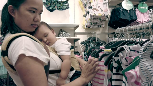 mother carrying her daughter shopping shirt at department store, sleeping baby - baby carrier stock videos & royalty-free footage