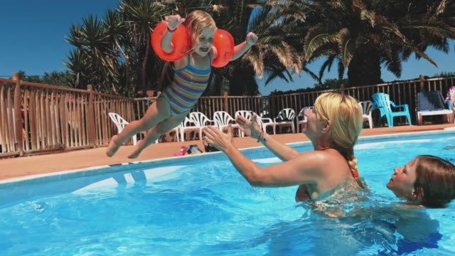 mother catching girl jumping into swimming pool - trust stock videos & royalty-free footage