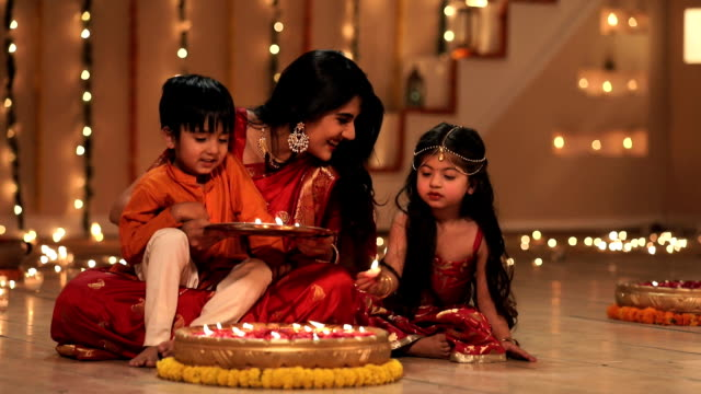 mother celebrating diwali festival with her children in the home, delhi, india - celebration stock videos & royalty-free footage