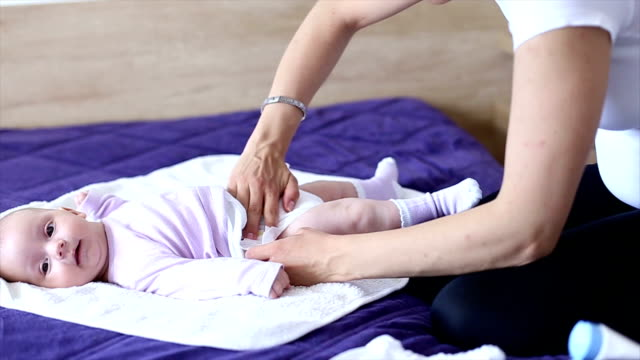 mother changes the diaper of her daughter - nappy stock videos & royalty-free footage