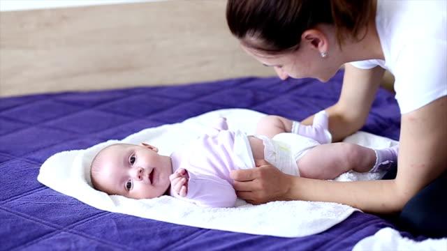vídeos y material grabado en eventos de stock de madre cambios del pañal de su hija - cambiar pañal