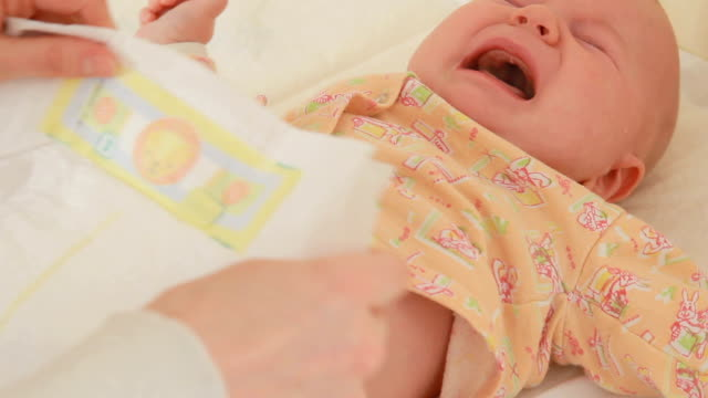 mother changing diaper to her crying baby - changing nappy stock videos & royalty-free footage