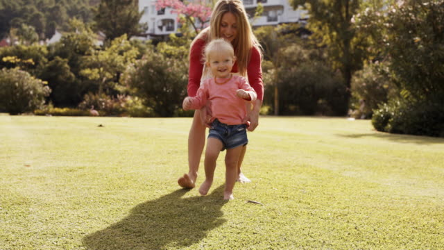 mother chasing daughter in park - toddler stock videos & royalty-free footage