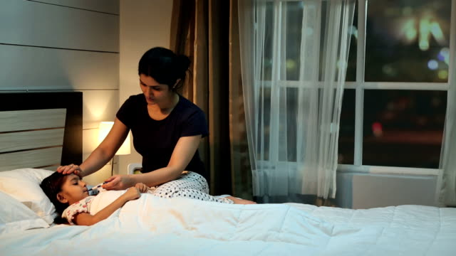 mother checking daughter temperature with digital thermometer, delhi, india - nightwear stock videos & royalty-free footage