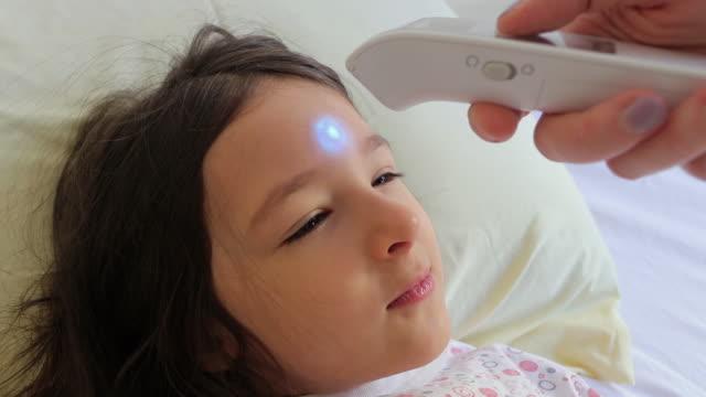 stockvideo's en b-roll-footage met moeder die de lichaamstemperatuur van de moeder met infrarode thermometer thuis controleert - dubbel bed