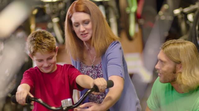 vidéos et rushes de mother checks bicycle price tag and boy nods in agreement - société de consommation