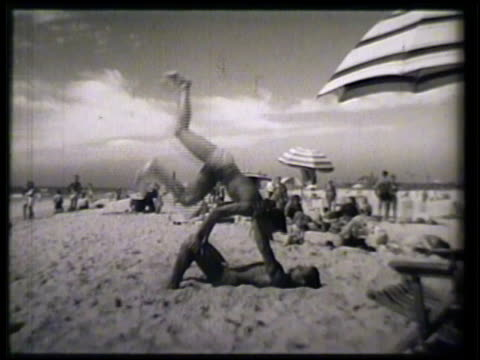 vidéos et rushes de mother & children, boy & girl, digging sand. male doing handstand on another male lying down. vs female sitting on beach talking, male playing w/... - 1952