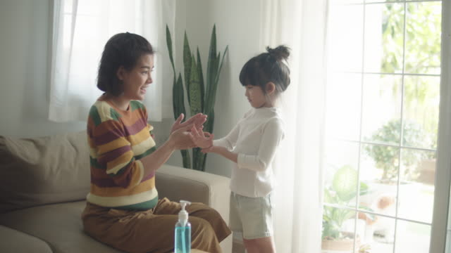 mother cleaning her daughter's hands with alcohol hand sanitizer protect her child from viruses - prevenzione delle malattie video stock e b–roll