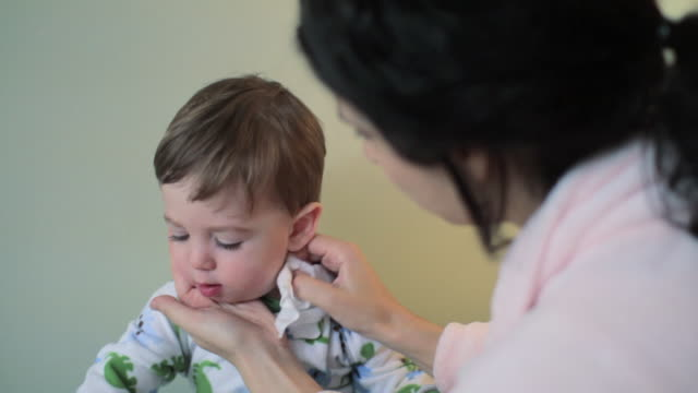 mother cleaning son's face with baby wipe - wet wipe stock videos & royalty-free footage