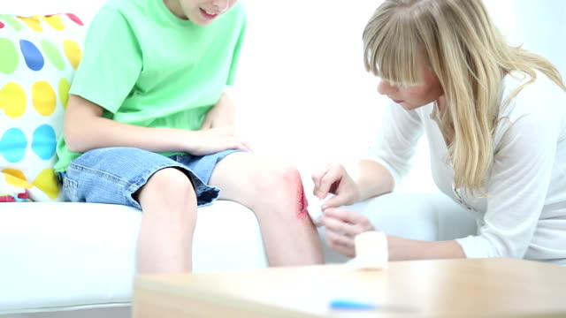 hd: mother cleaning sons scraped knee. - physical injury stock videos and b-roll footage