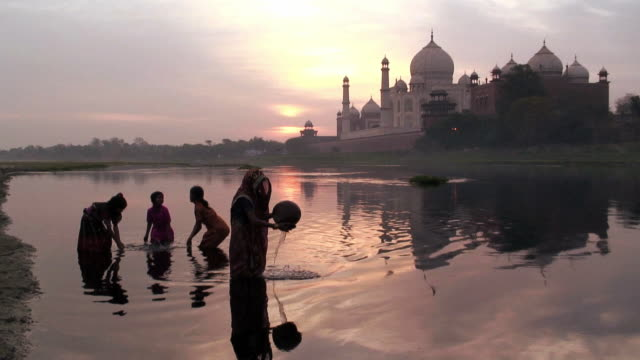 vídeos y material grabado en eventos de stock de ws mother collecting water, children playing in the river yamuna near taj mahal / agra, india - taj mahal