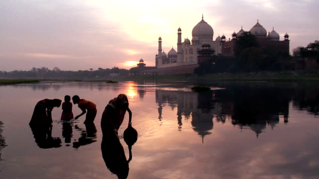 A mother collects water close to her children in the River Yamuna near the Taj Mahal in Agra, India.
