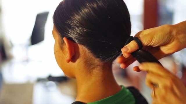 Mother combing a ponytail to her little girl .