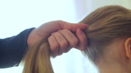 Mother combing daughter's hair