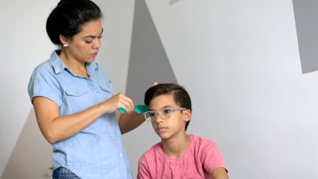 vídeos de stock e filmes b-roll de mother combing her son's hair - sentar se