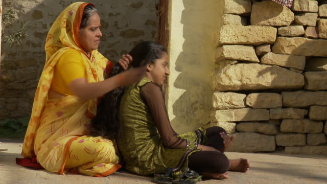 A mother combs her daughter's long hair.