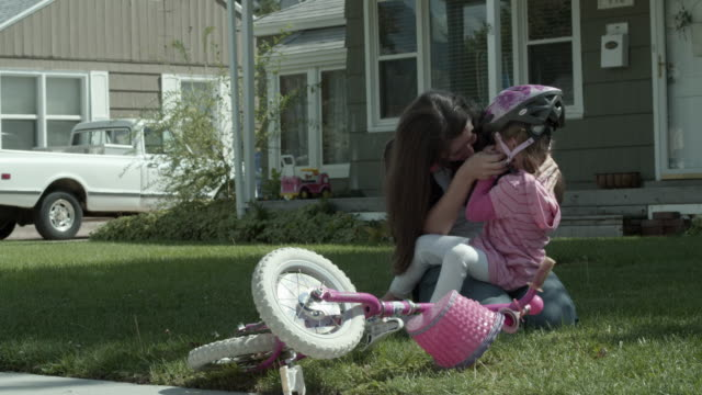 Mother conforting daughter after bike crash.
