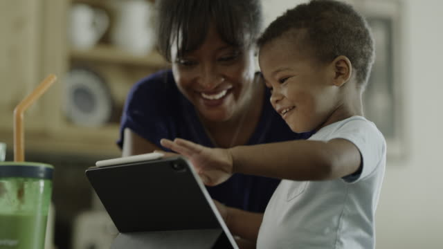 mother congratulating excited son learning to use digital tablet / orem, utah, united states - looking stock videos & royalty-free footage