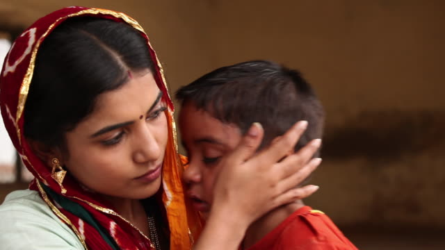 mother consoling her crying son, faridabad, haryana, india  - familie mit einem kind stock-videos und b-roll-filmmaterial