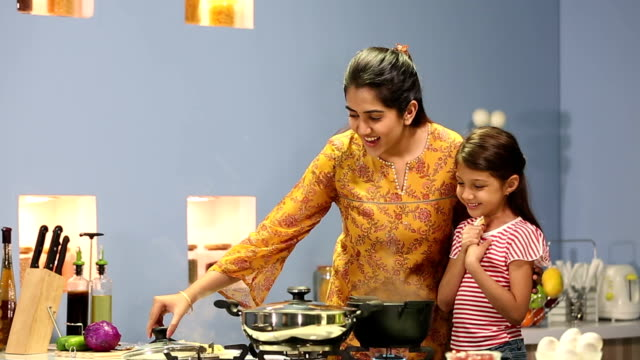 Mother cooking noodles with her daughter, Delhi, India