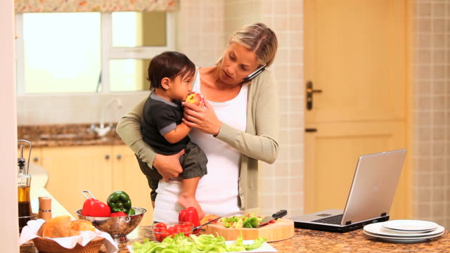 Mother coping with baby while cooking and using a laptop / Cape Town, Western Cape, South Africa
