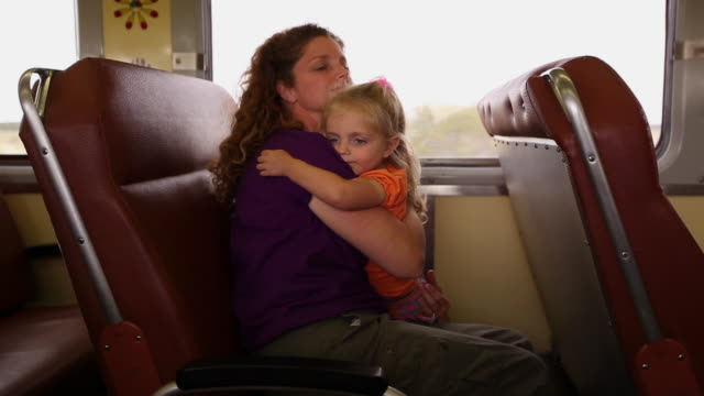 Mother cradles young daughter in her arms as they travel on a train