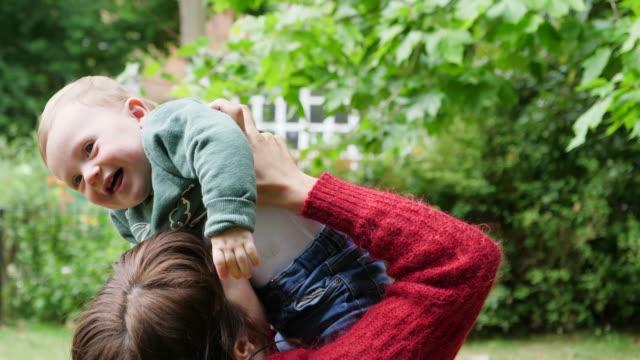 vídeos de stock e filmes b-roll de mother cuddling and kissing babyboy, babyboy laughing. - vida de bebé