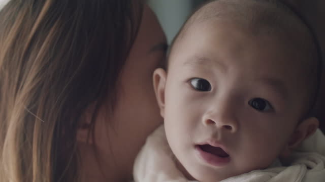 mother cuddling baby boy at home in front of window - south east asian ethnicity stock videos & royalty-free footage