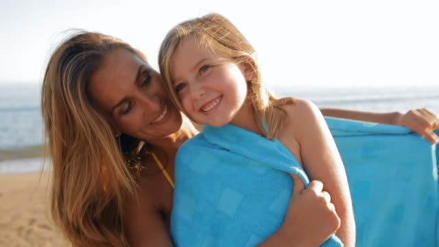 mother cuddling daughter on beach in blue towel - handduk bildbanksvideor och videomaterial från bakom kulisserna