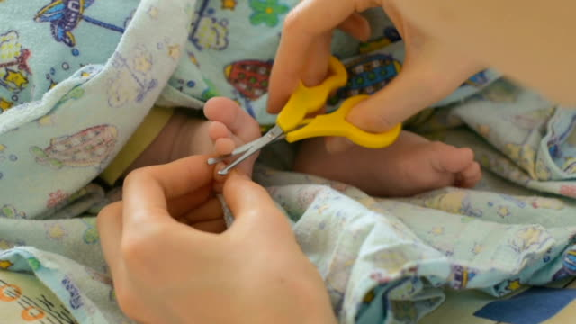 Mother cutting baby nails