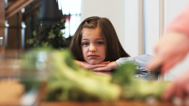 vídeos de stock e filmes b-roll de mother cutting broccoli while little girl looks on with a disgusted face - legumes