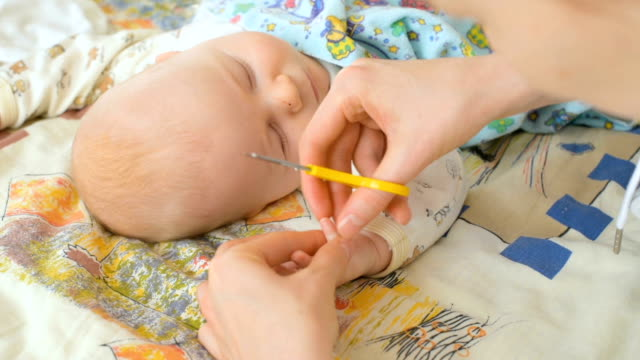 Mother cutting fingernails of baby