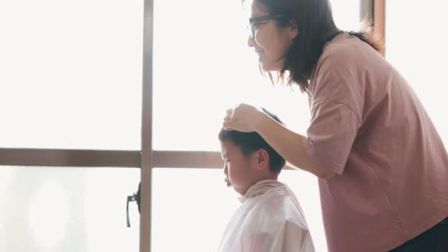 自宅で息子の髪を切る母親 - 思いやり点の映像素材/bロール